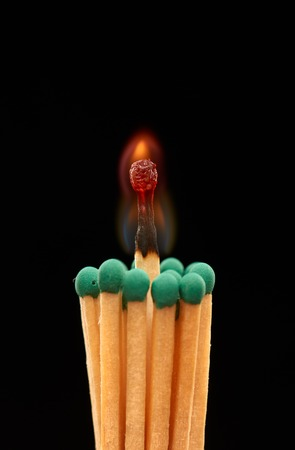 brilliant: Group of green wooden matches with burning match in the centre, isolated on black background Stock Photo