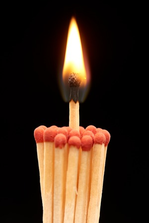 household accident: Group of red wooden matches with burning match in the centre, isolated on black background