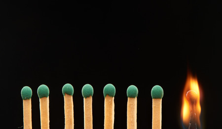 household accident: Set of seven green and one burning wooden matches isolated on black background Stock Photo