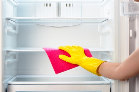 refrigerator with food: Womans hand in yellow rubber protective glove cleaning white open empty refrigerator with pink rag