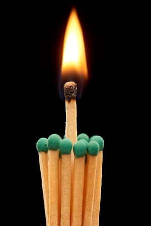 household accident: Group of green wooden matches with burning match in the centre, isolated on black background Stock Photo