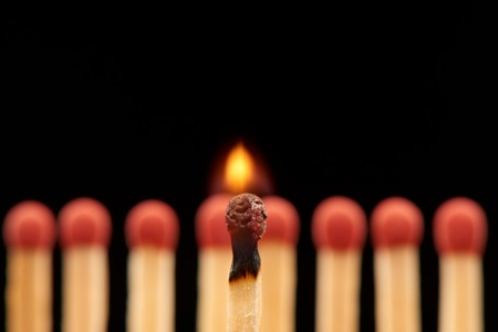 household accident: Burning match standing in front of defocused set of eight red wooden matches, isolated on black background