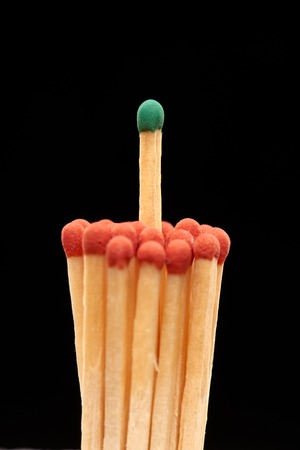 household accident: Group of red wooden matches with green match in the centre, isolated on black background