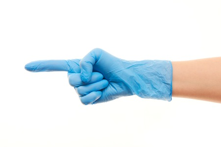 surgical glove: Close up of female doctors hand in blue sterilized surgical glove pointing on something against white background