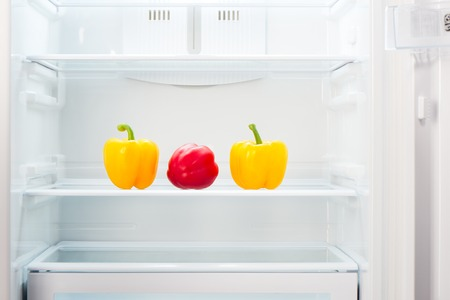 Two yellow and one red peppers on shelf of open empty refrigerator. Weight loss diet concept.