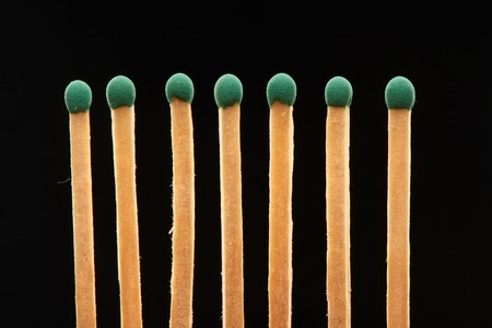 household accident: Set of seven green wooden matches isolated on black background Stock Photo