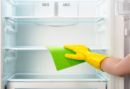refrigerator kitchen: Womans hand in yellow rubber protective glove cleaning white open empty refrigerator with green rag