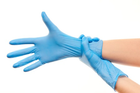surgical gloves: Close up of female doctors hands putting on blue sterilized surgical gloves against white background