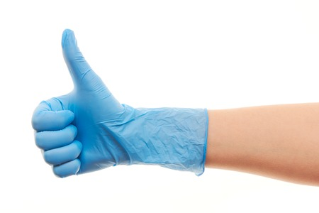 surgical glove: Close up of female doctors hand in blue sterilized surgical glove showing thumbs up sign against white background