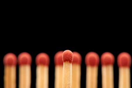 household accident: Red match standing in front of defocused set of eight red wooden matches, isolated on black background Stock Photo