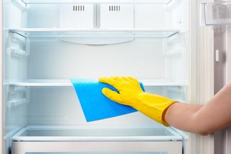 nevera: Mano de la mujer en el guante de protección de goma amarillo limpieza blanca abierta refrigerador vacío con el azul de trapo