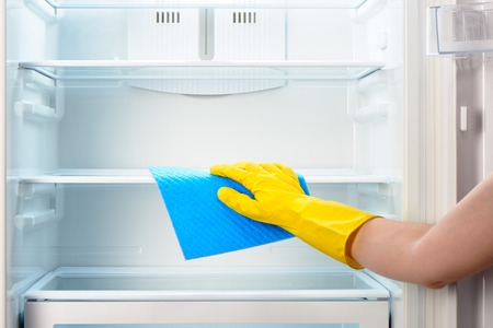 refrigerator with food: Womans hand in yellow rubber protective glove cleaning white open empty refrigerator with blue rag