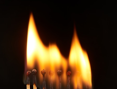 household accident: Set of eight burning wooden matches, isolated on black background