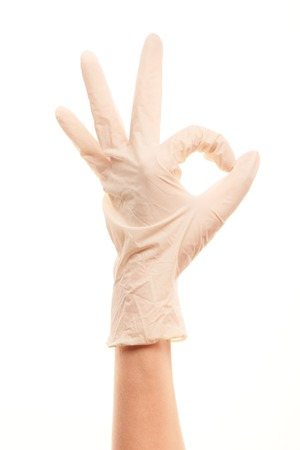 sterilized: Close up of female doctors hand in white sterilized surgical glove showing OK sign against white background