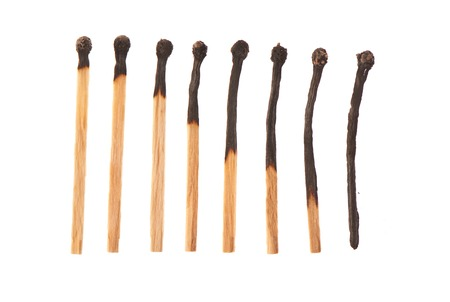 household accident: Set of eight burnt wooden matches arranged in ascending order isolated on white background