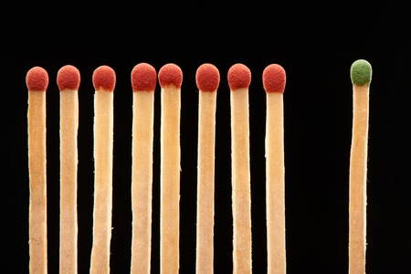 household accident: Set of eight red and one green wooden matches isolated on black background