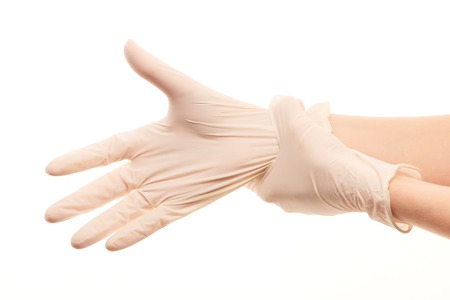 surgical gloves: Close up of female doctors hands putting on white sterilized surgical gloves against white background