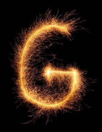 """letras negras: """"G"""" carta dibujada con destellos bengal� aisladas sobre fondo negro"""