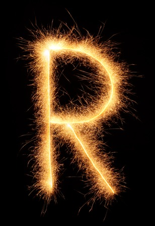 bengali: R letter drawn with bengali sparkles isolated on black background Stock Photo