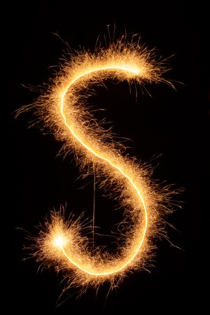 fire font: S letter drawn with bengali sparkles isolated on black background Stock Photo