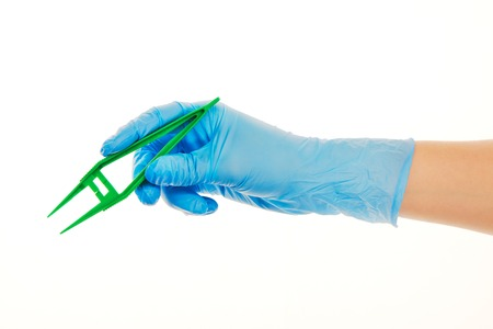 surgical glove: Close up of female doctors hand in blue sterilized surgical glove with green plastic forceps against white background