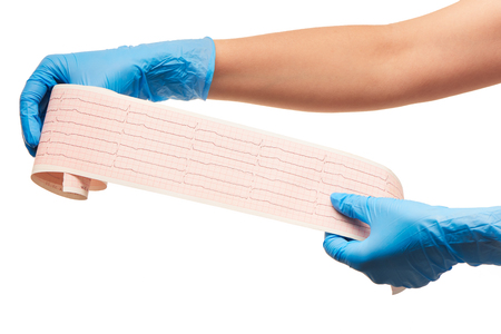 sterilized: Close up of female doctors hands in blue sterilized surgical gloves with ECG results on paper against white background Stock Photo
