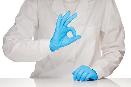 surgical gloves: Close up of female doctor in white medical gown and blue sterilized surgical gloves showing OK sign