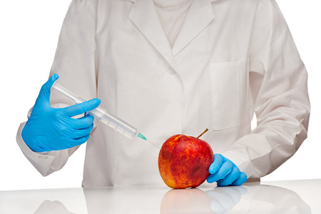 bad apple: Close up of female doctor in white medical gown and blue sterilized surgical gloves makes injection to bad looking apple with plastic syringe Stock Photo