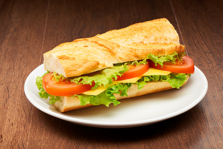 Tomato, cheese and salad sandwich from fresh baguette on white ceramic plate on dark wooden table background