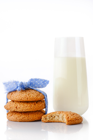 oatmeal cookie: Stack of three homemade oatmeal cookies tied with blue ribbon in small white polka dots, bitten cookie and glass of milk, isolated on white background