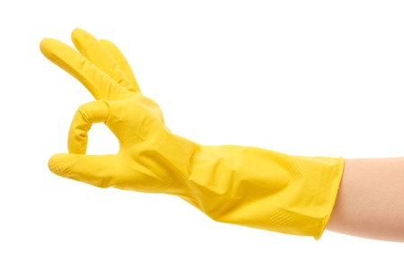 service occupation: Close up of female hand in yellow protective rubber glove showing OK sign against white background Stock Photo