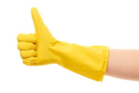 mujer limpiando: Cerca de la mano femenina en guante de goma amarillo de protecci�n que muestra los pulgares para arriba signo contra el fondo blanco Foto de archivo