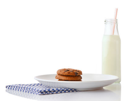 ceramic bottle: Stack of three homemade chocolate chip cookies on white ceramic plate on blue napkin and bottle of milk with straw, isolated on white background Stock Photo