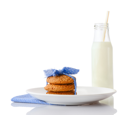 ceramic bottle: Stack of three homemade oatmeal cookies tied with blue ribbon in small white polka dots on white ceramic plate on matching blue napkin and bottle of milk with straw, isolated on white background