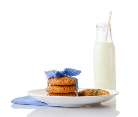 ceramic bottle: Stack of three homemade oatmeal cookies tied with blue ribbon in small white polka dots and bitten cookie on white ceramic plate on  napkin and bottle of milk with straw, isolated on white background Stock Photo