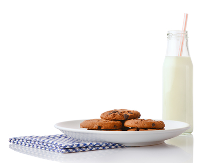 ceramic bottle: Pile of homemade chocolate chip cookies on white ceramic plate on blue napkin and bottle of milk with straw, isolated on white background