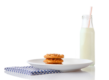 ceramic bottle: Stack of three homemade peanut butter cookies on white ceramic plate on blue napkin and bottle of milk with straw, isolated on white background