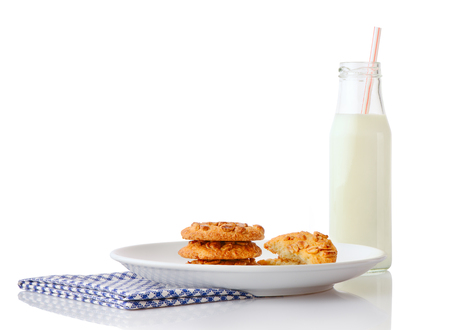 ceramic bottle: Stack of three homemade peanut butter cookies and halves of cookies on white ceramic plate on blue napkin and bottle of milk with straw, isolated on white background