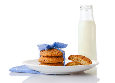 ceramic bottle: Stack of three homemade oatmeal cookies tied with blue ribbon in small white polka dots and halves of cookies on white ceramic plate on blue napkin and bottle of milk, isolated on white background