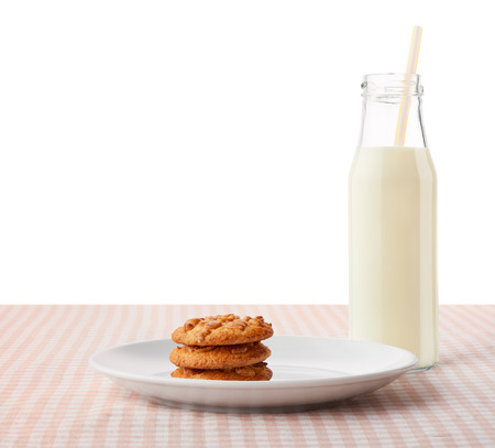 ceramic bottle: Stack of three homemade peanut butter cookies on white ceramic plate and bottle of milk with straw on classic brown and white checkered tablecloth, isolated on white background Stock Photo