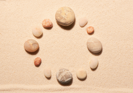 sand watch: Round frame of sea stones on sand. Summer beach background. View from above