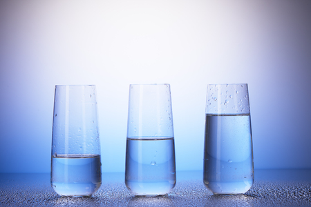 two and two thirds: One-third full, half-filled and two-thirds full drinking glasses with reflection in drops of water on white and blue background