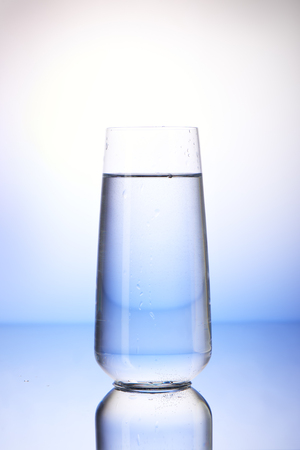 two and two thirds: Two-thirds full drinking glass with reflection on white and blue background