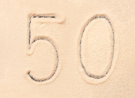 50 number: 50 number written on sand. Summer beach background