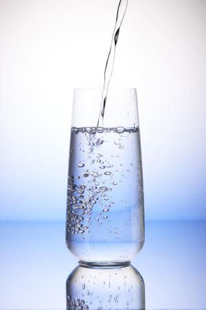 two and two thirds: Water pouring into two-thirds full drinking glass with reflection on white and blue background