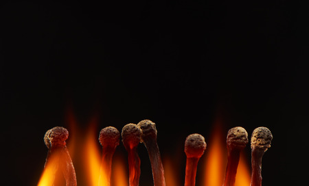 Set of eight burning wooden matches, isolated on black background
