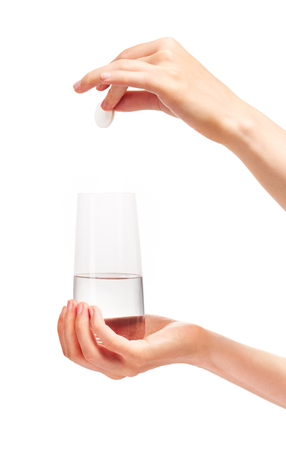 Close up of female hand holding large white round effervescent tablet over clean transparent drinking glass with water against white background. Stock Photo