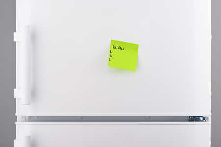 Template for to do list on green sticky note paper on white refrigerator door
