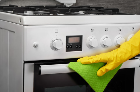 technic: Womans hand in yellow rubber protective glove cleaning white gas stove with green rag on gray background Stock Photo