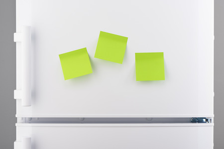 refrigerator: Three blank green sticky paper notes on white refrigerator door